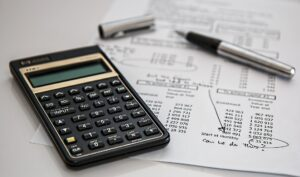 processing accounts payable invoices with paper and calculator